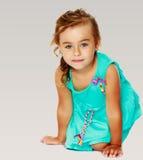 Kleines Mädchen im blauen Kleid auf ihren Knien Lizenzfreie Stockbilder