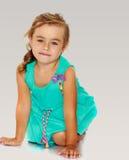 Kleines Mädchen im blauen Kleid auf ihren Knien Stockfoto