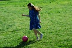 Kleines Mädchen im blauen Kleid, das Fußball auf grünem Gras tritt stockfotos