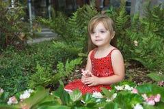 Kleines Mädchen im Blumenbett lizenzfreie stockbilder