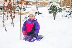 Kleines Mädchen im bunten Klagenspiel im Schnee im Hinterhof in der Kälte Lizenzfreie Stockfotografie