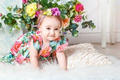 Kleines Mädchen im bunten Kleid mit Blumen stockfoto