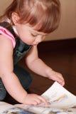 Kleines Mädchen im Denimoverall liest Buch Stockfotografie