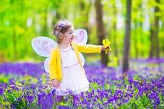 Kleines Mädchen im feenhaften Kostüm auf dem blauen Glockengebiet Stockbilder