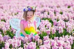 Kleines Mädchen im feenhaften Kostüm, das auf dem Blumengebiet spielt Stockfotos