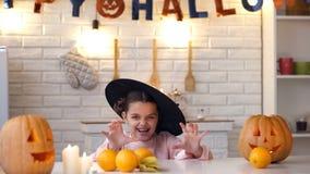 Kleines Mädchen im furchtsamen Hexenkostüm, das versucht, Kinder, Halloween-Partei zu erschrecken lizenzfreie stockbilder