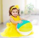 Kleines Mädchen im gelben Kleid mit großem Ball stockfotos