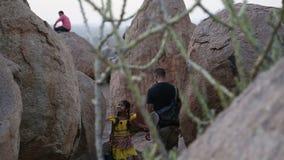 Kleines Mädchen im gelben Kleid und im Mann, die zwischen große Steine in Hampi geht stock footage