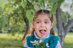 Kleines Mädchen im grünen Garten am sonnigen Tag Stockbild