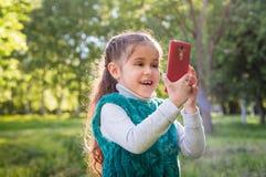 Kleines Mädchen im grünen Garten am sonnigen Tag Lizenzfreies Stockfoto