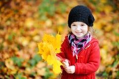 Kleines Mädchen im hellen roten Mantel am Herbst lizenzfreie stockfotografie