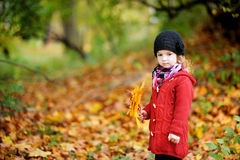 Kleines Mädchen im hellen roten Mantel am Herbst stockfoto
