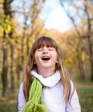 Kleines Mädchen im Herbstwald laut lachend Stockfotografie