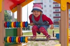 Kleines Mädchen im Hut klettert auf Kinderspielplatz an sonnigem Stockfotos