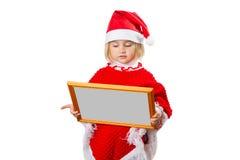 Kleines Mädchen im Hut Santa Claus, die Rahmen mit einem grauen backgro hält Stockbilder