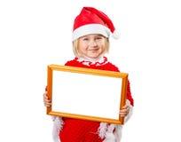 Kleines Mädchen im Hut Santa Claus, die Rahmen mit einem weißen backgr hält Lizenzfreies Stockfoto