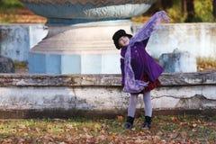 Kleines Mädchen im Hut wirft mit Schal am Herbsttag auf Stockbild