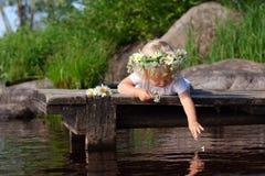 Kleines Mädchen im Kamillenkranz lässt Blumenblätter in das Wasser fallen Stockfotografie