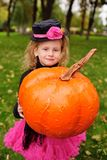 kleines Mädchen im Karnevalskostüm mit Kürbis Halloween feiernd stockbild