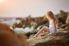 Kleines Mädchen im Kleid sitzt auf dem Strand durch das Meer bei Sonnenuntergang Stockfotografie