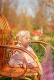 Kleines Mädchen im Kleid und mit einer Blume, die auf einem Stuhl sitzt Lizenzfreie Stockbilder