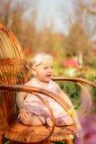 Kleines Mädchen im Kleid und mit einer Blume, die auf einem Stuhl sitzt Lizenzfreies Stockfoto