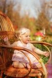 Kleines Mädchen im Kleid und mit einer Blume, die auf einem Stuhl sitzt Stockfoto
