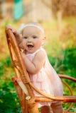 Kleines Mädchen im Kleid und mit einer Blume, die auf einem Stuhl steht Lizenzfreie Stockfotografie