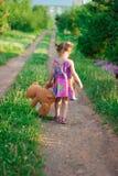 Kleines Mädchen im Kleid und mit einer Blume, die auf einem Stuhl steht Stockbilder