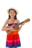 Kleines Mädchen im Kleid, welches die Ukulele spielt Lizenzfreie Stockfotografie