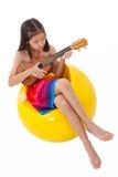Kleines Mädchen im Kleid, welches die Ukulele spielt stockfotografie