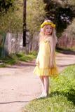 Kleines Mädchen im Löwenzahn Wreath Stockfoto