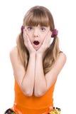 Kleines Mädchen im orange Kleid, das überrascht schaut stockbilder