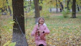 Kleines Mädchen im Parkherbst Entzückendes kleines Mädchen-Lächeln stock footage