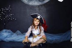 Kleines Mädchen im Piratenkostüm Ein grimmiger Minireaper, der eine Sense anhält, steht auf einem Kalendertag, der glückliches Ha Stockfoto