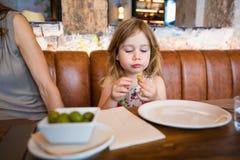 Kleines Mädchen im Restaurant, das in der Hand olivgrün schaut Lizenzfreie Stockfotografie