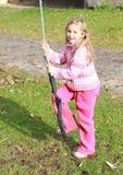 Kleines Mädchen im Rosa auf einem Schwingen Stockfotografie