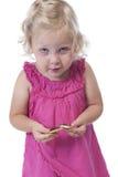 Kleines Mädchen im Rosa einen Keks essend, lokalisiert auf Weiß Lizenzfreies Stockfoto