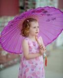 Kleines Mädchen im rosa Kleid mit Sonnenschirm Stockfoto