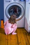 Kleines Mädchen im Rosa passt besorgt ihre Decke in der Waschmaschine auf stockfoto