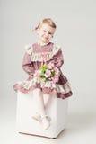 Kleines Mädchen im rosa-violetten Kleid und im Blumenstrauß blüht Stockfoto