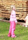 Kleines Mädchen im Rosa vor Holz Stockbild