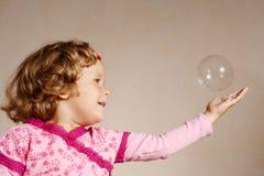 Kleines Mädchen im rosafarbenen Kleid mit einer Luftblase Lizenzfreie Stockbilder