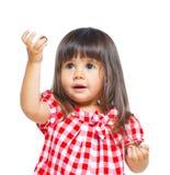 Kleines Mädchen im Rot, das lustiges Gesicht bildet. Stockfoto