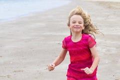 Kleines Mädchen im roten Kleid, das auf den Strand läuft Stockbilder