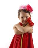 Kleines Mädchen im roten Kleid einen roten Gerbera umfassend lokalisiert Stockfotos