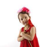 Kleines Mädchen im roten Kleid einen roten Gerbera umfassend lokalisiert Stockbilder