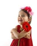 Kleines Mädchen im roten Kleid einen roten Gerbera umfassend lokalisiert Lizenzfreies Stockfoto