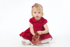 Kleines Mädchen im roten Kleid mit Geschenkbeutel Lizenzfreies Stockbild
