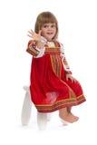 Kleines Mädchen im roten Trachtenkleid auf einem Stuhl Stockfotos